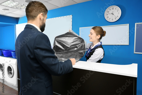 Young man receiving his clean suit from laundry worker at reception