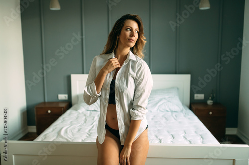 Portrait of beautiful young woman standing in bedroom - 205903500