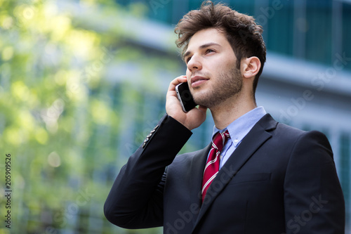 Wall mural Young manager on the phone outdoor