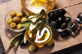 Bottle virgin olive oil and oil in a bowl with some olives - 205910772