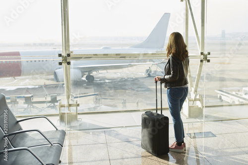 Rear view shot of a woman standing with luggage at the airport and looking through the glass window.
