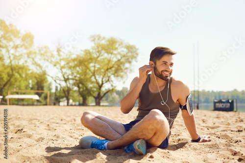 A bearded sportsman is sitting on the sand on the beach in the park.