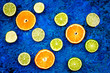 Fruit pattern. Oranges and lime round slices composition on blue background top view