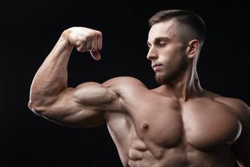 Handsome power athletic man bodybuilder demonstrates his biceps. © Restyler