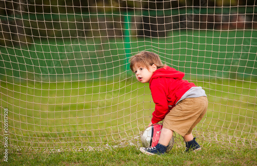 Fotobehang Voetbal the boy with the ball in the football goal