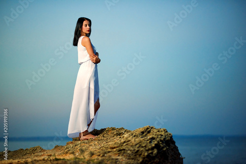 Young beatiful girl wearing white dress standing on rock near blue sea. Looking on amazing sideview, horizone. Feeling good, free, concentrated. Summer, warm, good weather.