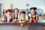 Funny children in the uniform of cooks on the table in vegetables in the kitchen. - 205927387