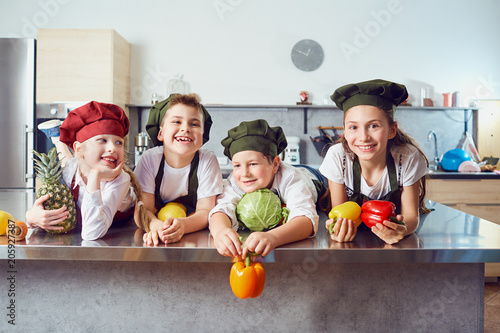 Foto Murales Funny children in the uniform of cooks on the table in vegetables in the kitchen.
