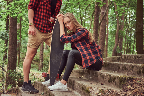 Young hipster couple, handsome man and blonde girl with a skateboard, sitting on steps in a park.