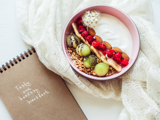 Healthy food. Berry smoothie, muesli with nuts, dry berries, pieces of banana and kiwi in a pink plate, branch of beautiful, blooming flowers, notebook with an inscription on a stylish table. Top view