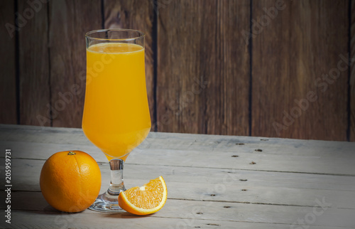 isolated and whole orange with juice on wooden table background