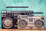 Retro designed ghetto blaster stereo boombox radio receivers with cassette recorders from circa 80s front textured aquamarine wall background. Listening music concept. Vintage old style filtered photo - 205966367