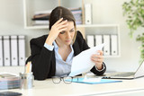 Worried executive reading a letter at office - 205972506