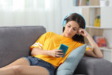 Relaxed girl in yellow listening to music at home - 205974302
