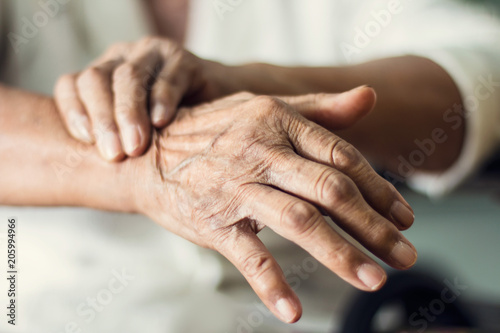 Close up hands of senior elderly woman patient suffering from pakinson's desease symptom. Mental health and elderly care concept © ipopba