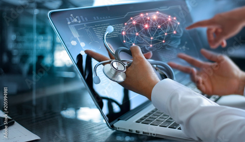 Medicine doctor team meeting and analysis. Diagnose checking brain scan with modern virtual screen interface on laptop with stethoscope in hand, Medical technology network connection concept. © ipopba