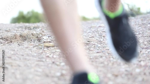 Close up of feet as runner jogs towards camera on gravel path