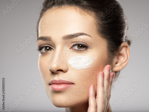 Beautiful face of young woman with cosmetic cream on face