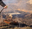 Quadro A man extinguishes the burning grass with water
