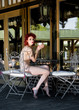 Beautiful redhead nude woman sitting on the terrace near the house