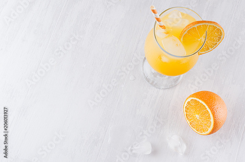 Colorful orange cool citrus cocktail with slice oranges, ice cube, straw on white modern wooden background, top view.