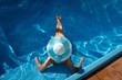 beautiful young woman in wide-brimmed blue hat sunbathing lying in the pool with turquoise clear water
