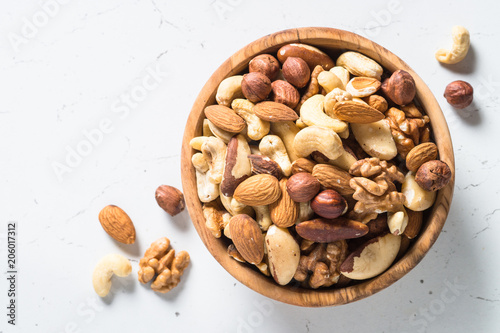 obraz lub plakat Nuts assortment in a bowl on white top view.