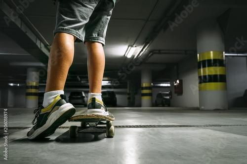 Boy on skateboard skates in undeground parking close up image