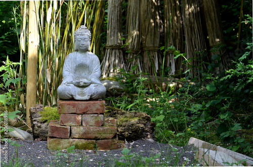 Canvas Boeddha Buddha stone statue in a green garden