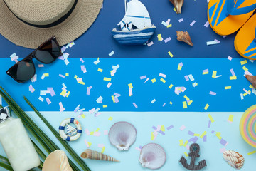 Flat lay objects the accessory for travel summer holiday background concept.Table top view of fashion clothing to traveler at beach.Essential items on modern blue sea paper.Free space for content.