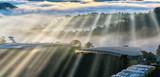 Beautiful sunrise through the fog with long shadows and sunbeams