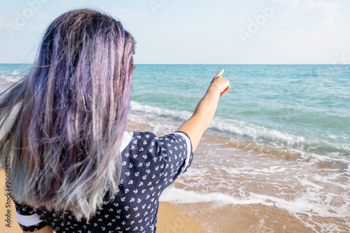 Foto Murales Woman pointing at the sea, copy-space.