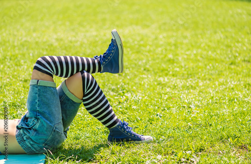Fototapeta Legs in black and white striped stockings and blue sneakers on the grass in the park. Chilling concept