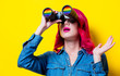 Young pink hair girl in blue shirt holding a binoculars with rainbow. Portrait on isolated yellow background