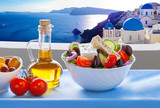 Greek salad against famous church in Oia village, Santorini island in Greece - 206035534