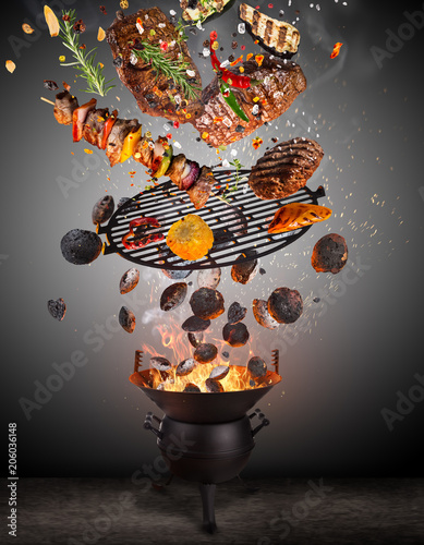 Kettle grill with hot briquettes, cast iron grate and tasty skewers flying in the air. - 206036148