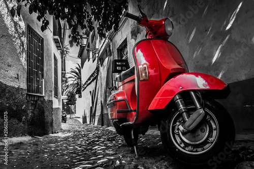 Aluminium Scooter Red vespa scooter parked in an old empty paved street