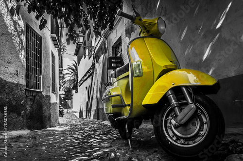 Plexiglas Scooter Yellow vespa scooter parked in an old empty paved street