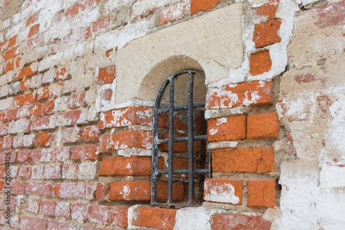 Fototapeta Window with a lattice in a brick wall of the monastery