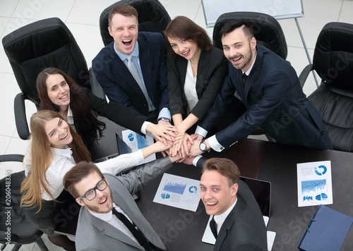 Wall mural business team with hands clasped together on Desk