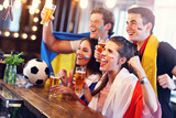 Group of friends watching soccer in pub - 206050956