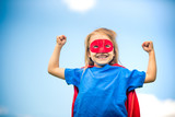 Funny little girl playing power super hero over blue sky background. Superhero concept. - 206053320