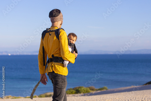 Foto Murales Modern parenting. Dad with baby daughter in  a carrier in the beach