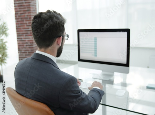 businessman sitting at his desk and making a financial report.