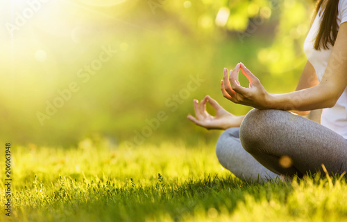 Leinwanddruck Bild Yoga woman meditating at sunset. Female model meditating in serene harmony