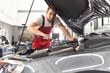 Portrait KFZ-Mechaniker repariert Auto in einer Werkstatt // Car mechanic repairs car in a workshop