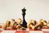 Black chess queen beats whites on chessboard