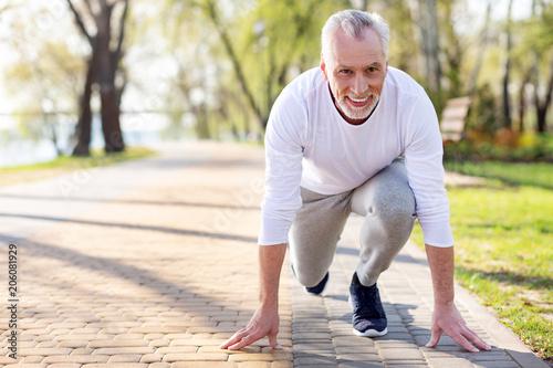 Fotobehang Hardlopen Ready to start. Nice positive man smiling while being ready to start running