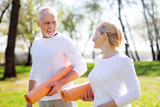 Ready for workout. Active healthy couple holding yoga mats while going together to the training - 206083341