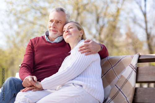 Pleasant relaxation. Positive happy couple sitting together on the bench while resting in the park